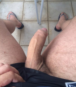pulling shorts aside to reveal long uncut cock